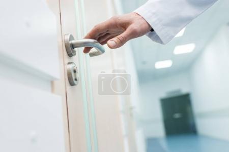 Photo pour Vue recadrée homme médecin Tenez la poignée de la porte à l'hôpital - image libre de droit