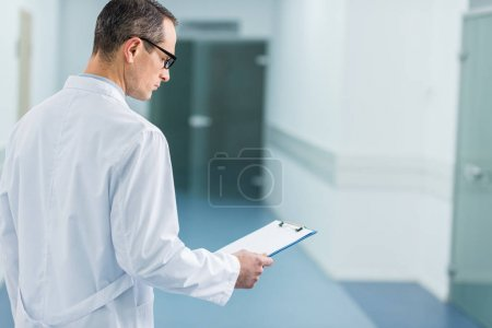 male doctor in white coat reading diagnosis in hospital