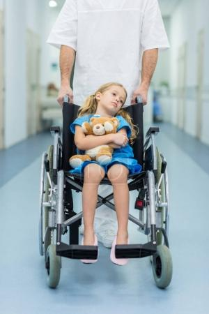cropped image of doctor moving kid on wheelchair