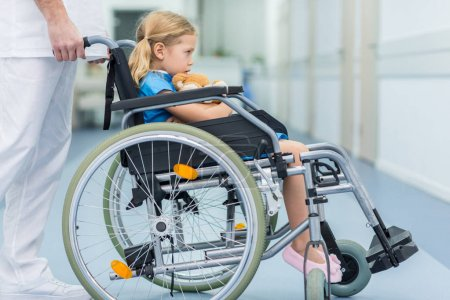 Photo for Side view of doctor moving kid on wheelchair - Royalty Free Image
