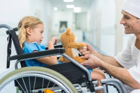 side view of doctor and patient on wheelchair holding hands