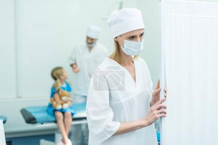 doctors preparing kid for surgery in operating room