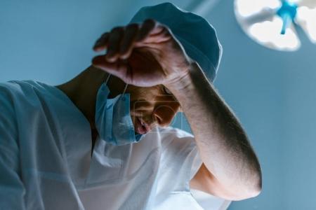 Photo pour Vue du bas du médecin fatigué dans la salle d'opération - image libre de droit