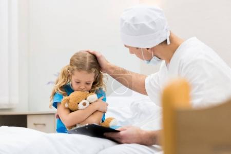 doctor palming head of worried kid with soft toy