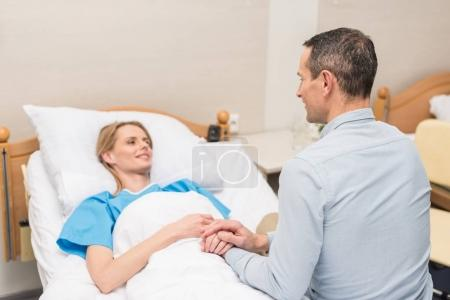 husband holding hands with sick wife