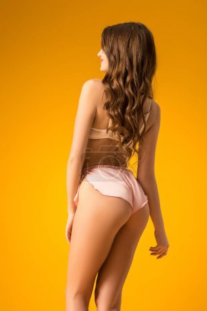 rear view of sexy girl posing in lingerie set isolated on orange