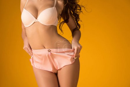 cropped image of sexy girl taking off panties isolated on orange