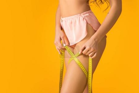 cropped image of sexy girl in panties measuring hip isolated on orange