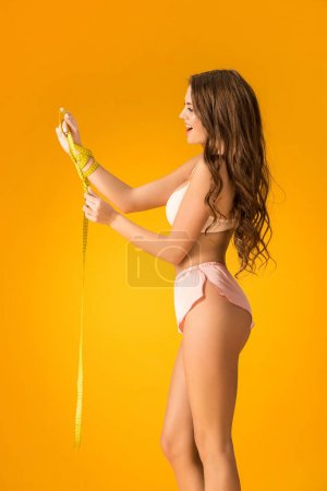 Photo for Side view of surprised sexy girl in lingerie set looking at tape measure isolated on orange - Royalty Free Image