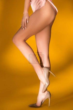 cropped image of female naked legs on orange