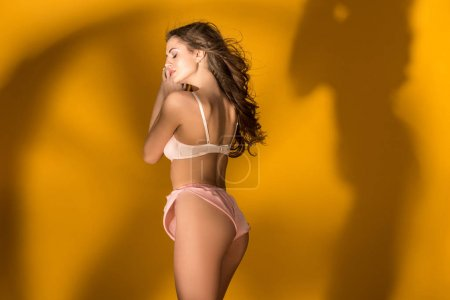 side view of sexy girl standing in lingerie set with shadow silhouette on wall on orange