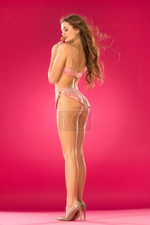 Photo for Side view of sexy girl with lollipop on pink - Royalty Free Image