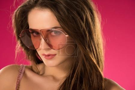portrait of attractive girl in sunglasses looking at camera isolated on pink
