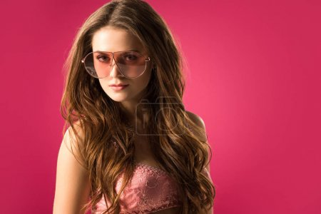Photo for Portrait of attractive girl in sunglasses and bra looking at camera isolated on pink - Royalty Free Image