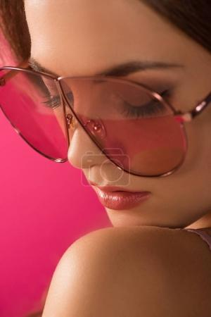 portrait of attractive girl in sunglasses with closed eyes isolated on pink