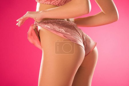 cropped image of female butt in panties isolated on pink