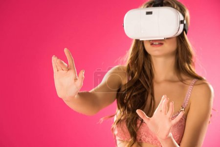 Photo for Seductive woman in underwear touching something with virtual reality headset isolated on pink - Royalty Free Image
