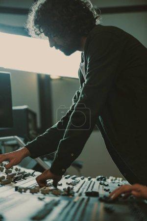 Photo pour Beau jeune producteur sonore travaillant avec l'appareil de contrôle - image libre de droit