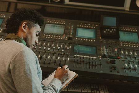 handsome young musician writing in notebook at recording studio
