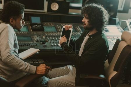 Photo for Man showing blank tablet screen to sound producer at recording studio - Royalty Free Image