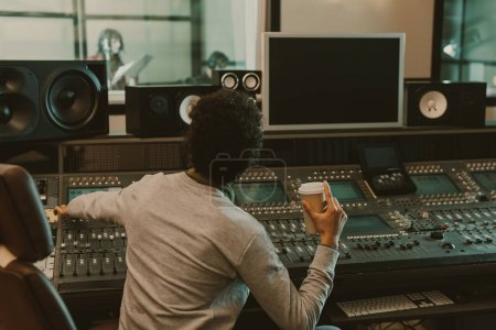 Photo for Sound producer with disposable cup of coffee working at studio - Royalty Free Image