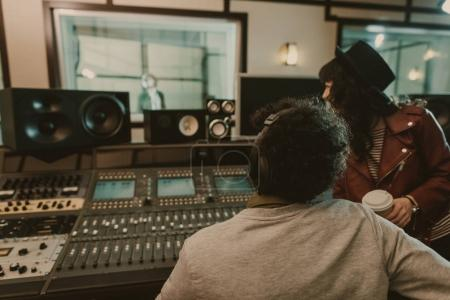 Photo for Sound producers looking at singer at recording studio - Royalty Free Image