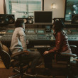 Sound producers sitting at recording studio and di...