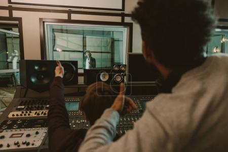 Photo for Sound producers showing thumbs up to singer at recording studio - Royalty Free Image