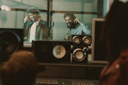 young handsome musicians recording song behind glass at studio and showing thumbs up