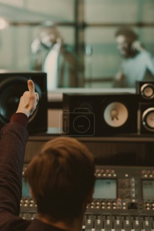Photo for Sound producer showing thumb up to singers behind glass at recording studio - Royalty Free Image