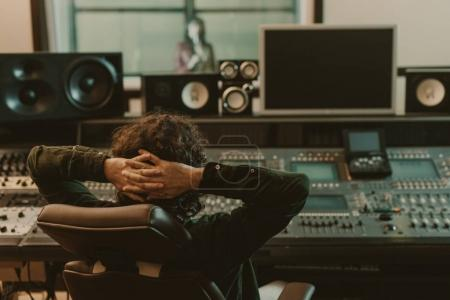 Sound producer relaxing in armchair at recording s...