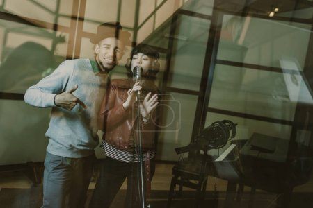 young singers couple recording song behind glass at studio