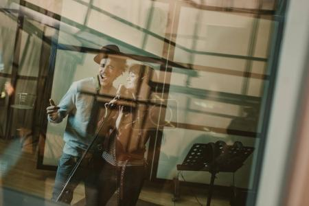Photo for Young talented singers couple recording song behind glass at studio - Royalty Free Image