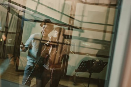 young talented singers couple recording song behind glass at studio