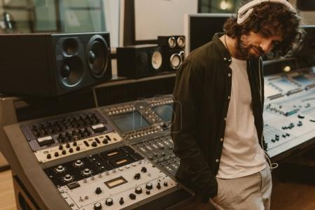 sound producer in headphones leaning back on recording equipment at studio