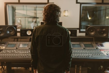 Photo for Back view of sound producer in headphones at studio - Royalty Free Image