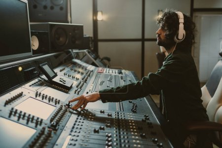 Photo for Side view of concentrated sound producer working at studio - Royalty Free Image