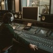 Постер, плакат: sound producer working at studio while recording song