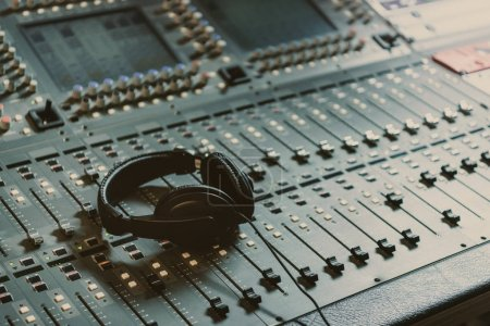 headphones on graphic equalizer at recording studio