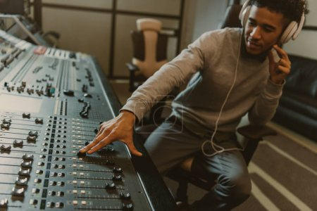 young handsome sound producer working with analog equalizer at studio