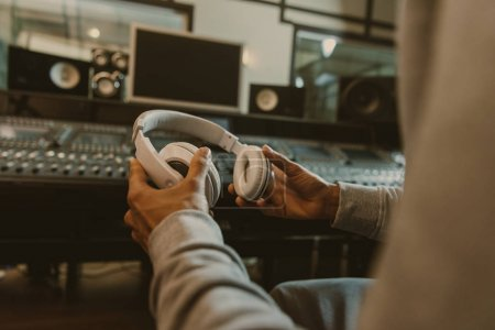 Photo for Cropped shot of sound producer with headphones sitting at studio - Royalty Free Image