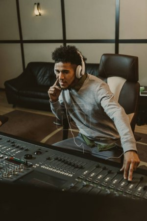 Photo for Smiling young sound producer sitting at studio - Royalty Free Image