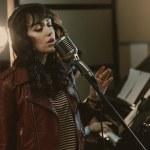Sensual female singer performing song at recording...