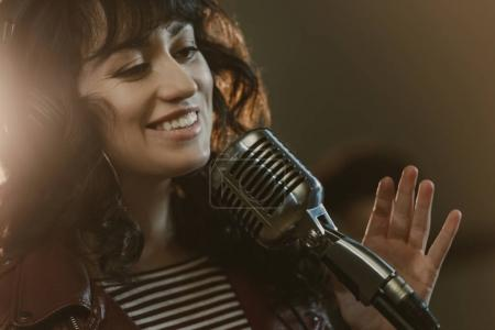 Attractive young female singer performing song and...
