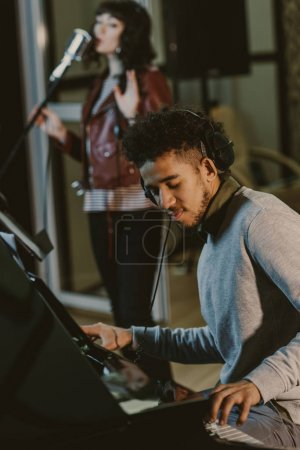 young african american musician playing piani while singer performing song on background