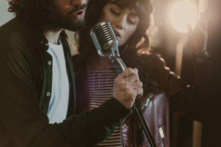 Photo pour Gros plan photo du jeune couple interprétant la chanson avec microphone vintage - image libre de droit