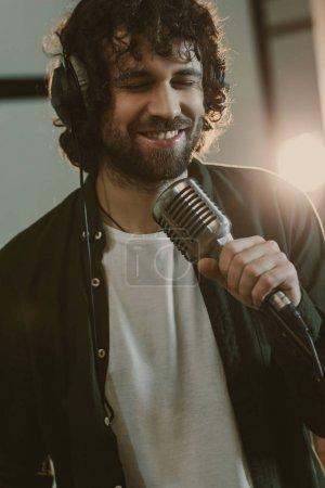 Photo pour Beau jeune chanteur en interprétant la chanson au studio de casque - image libre de droit