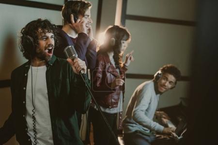 Photo pour Groupe de musique enregistrement chanson au studio tandis que l'homme jouer du piano - image libre de droit
