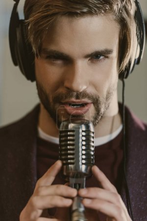 Photo for Close-up portrait of handsome young singer performing song and looking at camera - Royalty Free Image