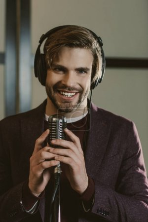 happy young singer in headphones standing with microphone